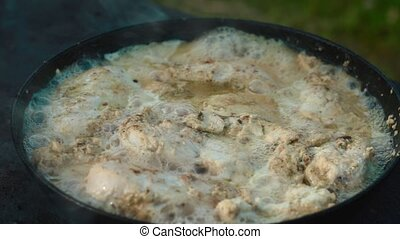 chicken meat in a frying pan outdoors