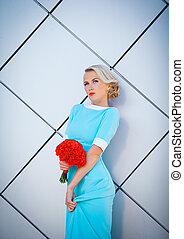 Daring blonde rebel with brightly painted lips. In a long blue dress with bouquet of red in hand. Against the background of the rectangular decorative walls.