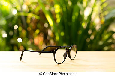 Hipster glasses on the table with plant in the background