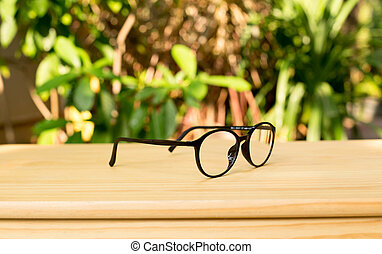 Hipster glasses on the wooden table with plant in the...