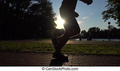 Male runner legs sunset silhouette. 4K steadicam video -...