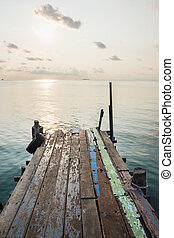 Wooden jetty bridge with seascape during sunrise