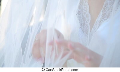 Amazing bride smiling and looking through the white veil