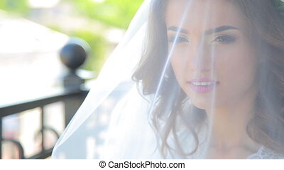 Face of the young beautiful bride lifting the white wedding...