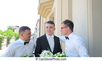 Groom with friends standing on a balcony in full HD