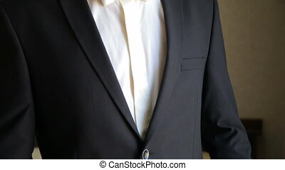 Handsome groom corrects the jacket in full HD
