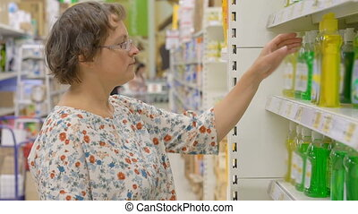 Young woman choosing cleanser in shop - Young Caucasian...