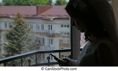 Pretty bride is using phone on the balcony in the evening in...