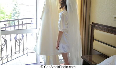 Beautiful bride touches wedding dress and removes it in full...