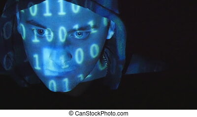 Close up shot of male face of hacker with binary code...