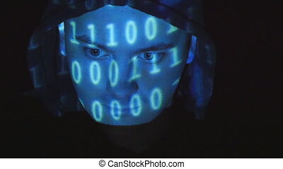 Hooded hacker working on a computer, binary code projecting...