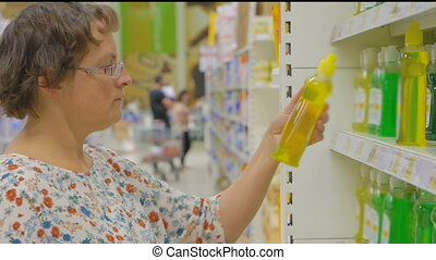 woman buys cleaning products in a supermarket - a young...