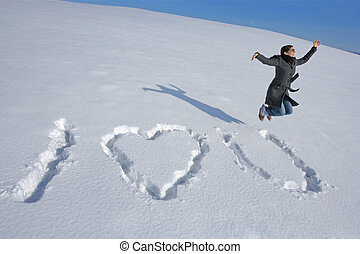 I love you in the snow - A happy woman jumping after writing...