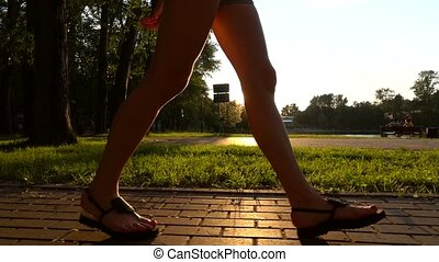 Slow motion steadicam shot of girl in sandals walking in...