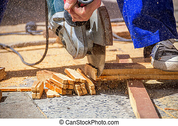 Worker cuts wood bars - Carpenter using an electric saw...