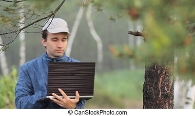 A man working on a laptop near a tree in the forest. Early...