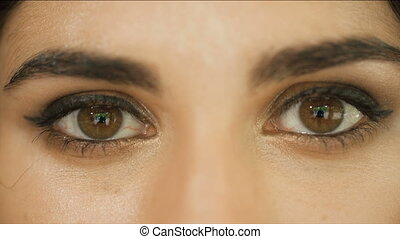 Sad womans eyes - Woman with brown eyes looks straight