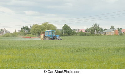 Tractor spray fertilize field with chemicals.