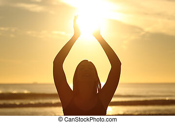 Woman holding sun at sunset - Front view of a back light of...