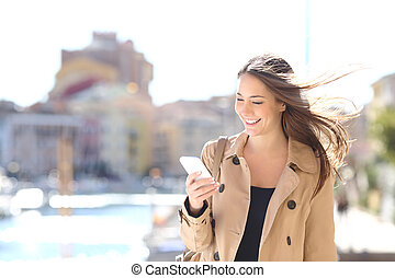 Happy woman walking and writing on a smart phone - Happy...