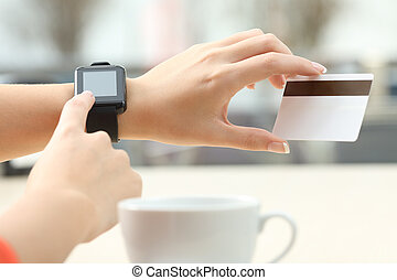 Girl buying online with credit card and smartwatch - Close...