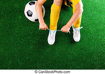Unrecognizable little football player against green grass,...