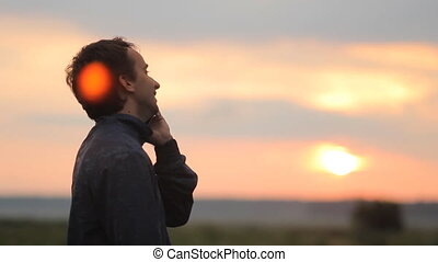 Man calling on the smart phone Beautiful sunset on the...