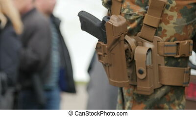 Military man with a gun on his leg. Close up
