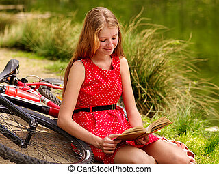 Bikes cycling girl into park read book bicycle on shore -...