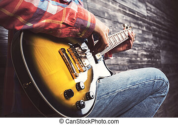Man playing guitar - Side view of casual man playing...