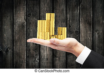 Hand holding coins - Businessman hand holding golden coin...
