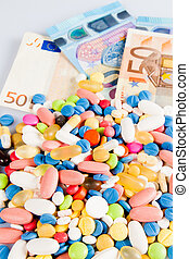 Pills of different colors on money