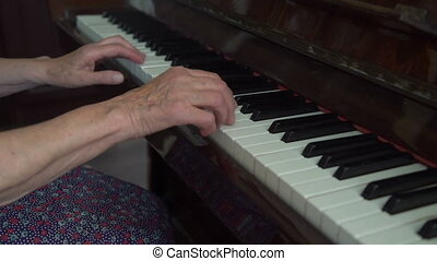 Old cute woman is playing the piano in the home