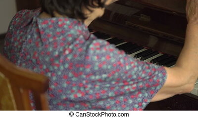 Old woman is playing the piano in home in full HD