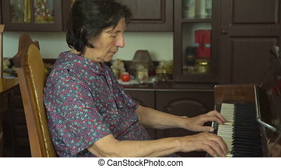 Old woman is playing the piano and looking on a camera in...