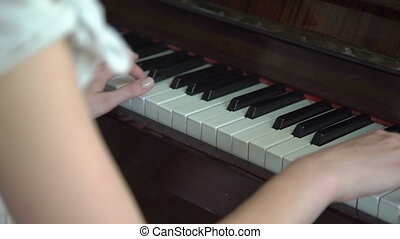 Young hands playing on the piano keyboard in full HD