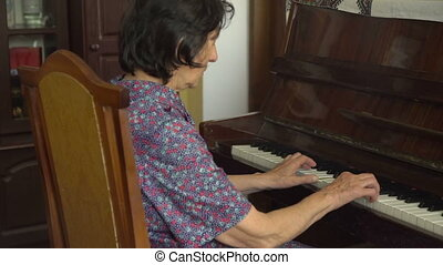 Old happy grandmother is playing the piano