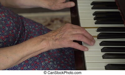 Old woman with wrinkled hands is playing the piano in full...