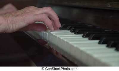 Old wrinkled woman's hands playing the piano. Close up in...