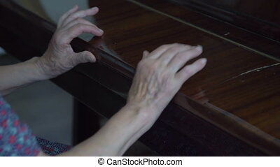 Grandmother opens the piano and starts to play in full HD