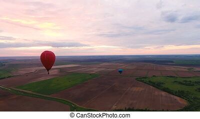 Hot air balloon in the sky over a fieldAerial view - Red...