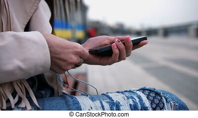 Close up on the hands of woman holding a smartphone, connecting headphones on the street - technology, music, communication concept