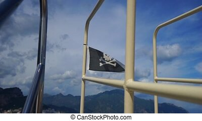 Pirate flag waving in wind against blue sky