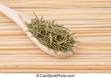 dried rosemary in wooden spoon and background