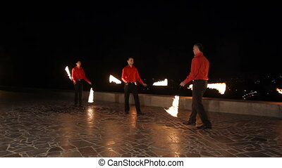 Fire show in the dark. - Men artists twist fiery circles on...