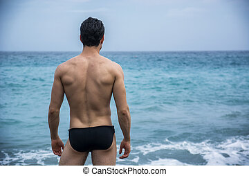 Back view of man in trunks against of seascape - Back view...