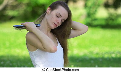 Woman touching her hair in the park on the green grass