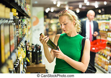 Woman shopping groceries at supermarket. - Beautiful...