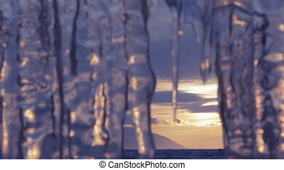 Setting sun is reflected in icicles. Photographers at...