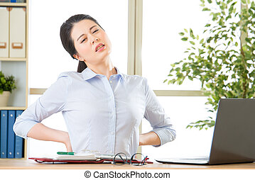 Young asian businesswoman with pain in back in office